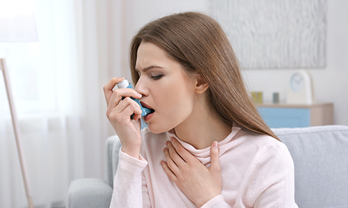 woman using a ventalin enhaller during an asthma attack