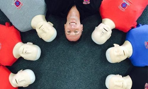 first aid trainer laying with CPR dummies