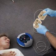 Heartsine Defibrillator being demonstrated on a patient lying on the floor