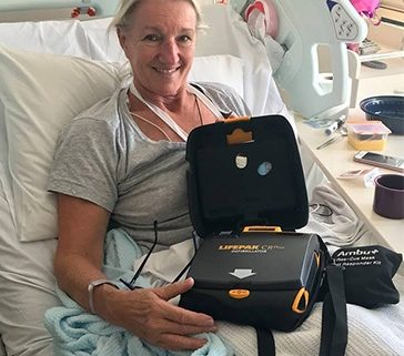 Woman in hospital bed with defibrillator that saved her life during a parkrun