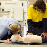 2 People performing Workplace First aid and CPR training on CPR dummy