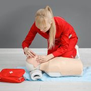 Woman in Red Jumpsuit performing CPR on training doll