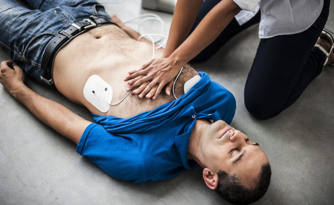 Performing CPR on a man with Defibrillator and Defibrillator Pads