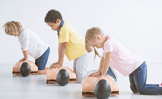 Children Learning how to perform CPR on CPR dummies