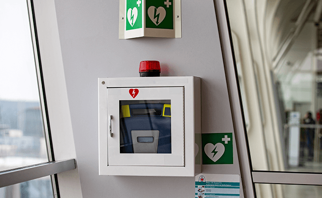 Defibrillator in an alarmed wall cabinet with AED signage in a public accessible location