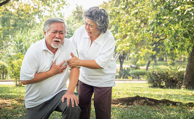 Elderly man having a heart attack on a golf course