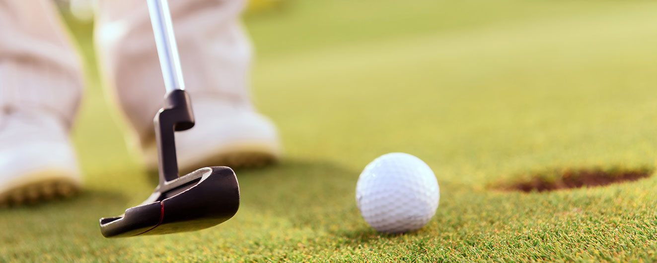 Close up of a golf ball and golf club